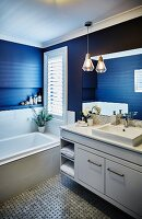 Washstand with white base cabinet next to fitted bathtub next to window in blue-painted bathroom