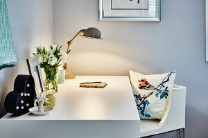 White desk lit by retro table lamp and chair with cushion