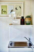 Stainless steel sink against white-tiled wall below shelf and framed triptych of birds on painted wall