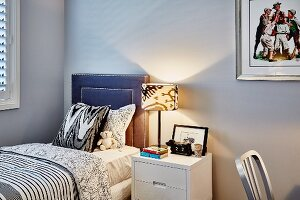 Table lamp on bedside table and single bed with leather-covered headboaard