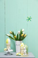 Pastel Easter arrangement; tulips in ceramic beaker, eggs and rabbit ornaments