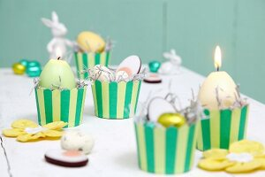 Easter arrangement in yellow and green; candles and sweets in stripe muffin cases