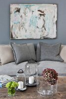 Sofa below modern artwork, candle lanterns and dried hydrangea flower on wooden table