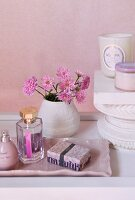 Cosmetics in pink dish in front of vase of pink flowers