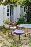Antique garden chair and metal garden table on terrace outside house