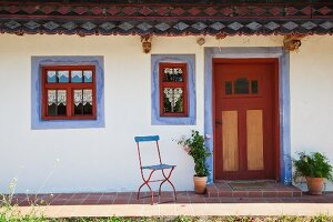 Ausschnitt eines alten, renovierten Bauernhauses mit blauen Faschen um Fenster und Tür