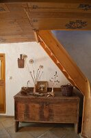 Rustic wooden trunk under staircase and painted wooden ceiling in hallway