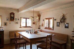 Restaurierte Bauernstube mit Eckbank um rustikalen Holztisch