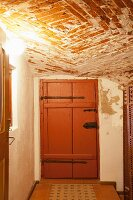 Cellar with rustic brick ceiling and brown board door with wrought iron fittings