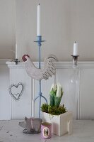 Romantic, country-house Easter arrangement of spring flowers and various candlesticks