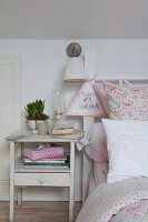 Shabby-chic bedside cabinet next to bed with floral bed linen and child's drawing hung from bedstead