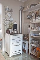 Old cooker and open-fronted shelves of crockery in vintage-style kitchen