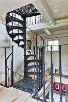 Hand-crafted, black vintage spiral staircase in rustic country house