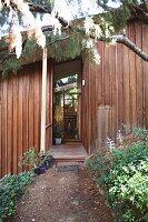 View from garden towards redwood timber house with open front door