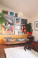 Dog on flokati rug and couch with ethnic blanket against half-height, continuous sideboard below collection of pictures on wall