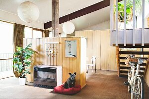 Retro gas heater in wood-clad partition; bicycle at foot of stairs