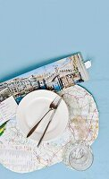 Place setting on place mat made from map and open Venice travel brochure