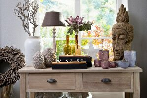 Various vases, flowers, tealight holders and Oriental stone head on wooden lowboy below window