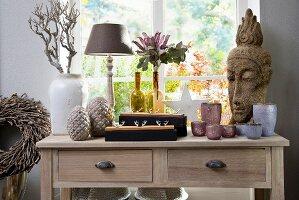 Verschiedene Vasen mit Blumen und Windlichter, seitlich Steinkopf in asiatischem Stil auf Holztisch vor Fenster