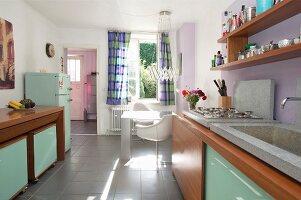 Retro Küche mit Holzfronten und mintgrüner Glasfüllungen, im Hintergrund Essplatz am Fenster