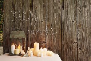 Lit candles on table and in lantern below Christmas greeting on board wall