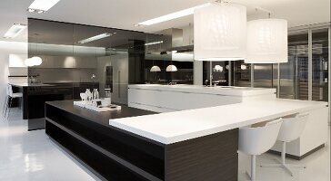 Designer kitchen with black and white elements - pendant lamps above table top mounted across wooden counters