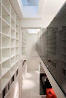 Open-plan, contemporary, double-height showroom house; white shelving with many compartments to one side