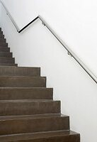 Staircase of dark grey, polished concrete with stainless steel handrail on wall