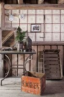 Old wooden crate in front of metal-framed side table and checked wallpaper in rustic attic interior