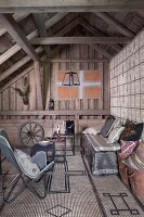 Butterfly armchair and bench with cushions on patterned sisal rug in rustic attic room with exposed wooden roof structure