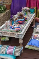 Low garden table with Indian-style table setting with coloured glasses and flowers and floor cushions on wooden decks