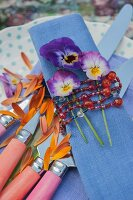 Violas on blue linen napkin tied with bead necklace