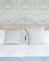 Cane headboard of bed with wooden frame against leaf-patterned wallpaper