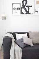 Various cushions and blanket on charcoal-grey couch below printed graphic artworks on white wall-mounted shelf
