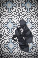 Ladies' black sandals on tiled floor with ornamental pattern