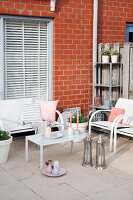 White outdoor furniture and silver Oriental lanterns on comfortable terrace next to brick façade