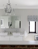 White, modern washstand with twin sinks, mirrored cabinet and half-height, exposed brick wall in modern, country-style bathrom