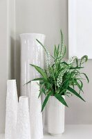 Collection of white vases; white flowers and leaves in one
