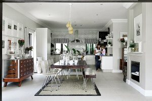 Dining table with matching bench and white chairs in open-plan interior; family in kitchen in background