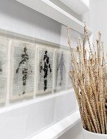 Dried stems in vase next to paintings on printed pages in white picture frame