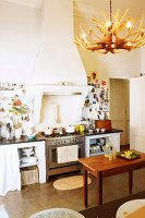Wooden table in front of kitchen counter with gas cooker below masonry mantel hood in traditional kitchen with lampshade made from antlers and decorated walls