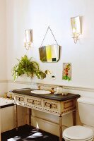 Antique, Rococo-style washstand and vintage mirror flanked by candle sconces in old-fashioned bathroom