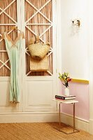 Dress hung on door of 50s-style fitted wardrobe, vase of flowers on small side table and sisal carpet in nostalgic interior