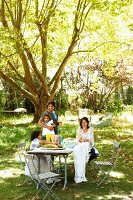 Family in sunny, summery garden around set table under shady tree