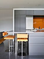 Orange bar stools at counter in grey modern kitchen
