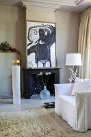 Flokati rug, white loose-covered armchair and fireplace below modern artwork in traditional interior