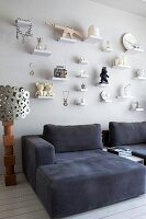 Comfortable, dark grey armchairs below ornaments on small bracket shelves