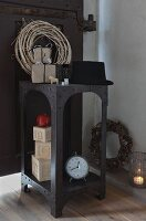 Christmas decorations and vintage alarm clock on retro iron shelves