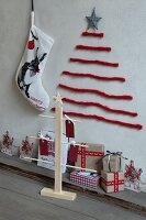 Stylised Christmas trees made from lengths of red wool on wall and made from wood, Christmas stocking with hare motif and wrapped gifts