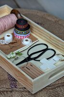 Ribbons with Scandinavian patterns, scissors and tags on wooden tray